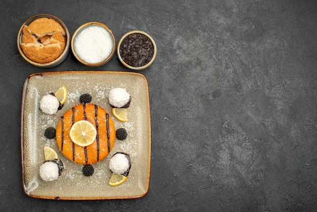 Draufsicht köstliches kuchendessert mit zitronenscheiben und kokosbonbons auf dunklem kuchendessert süßer kuchensüßigkeitstee