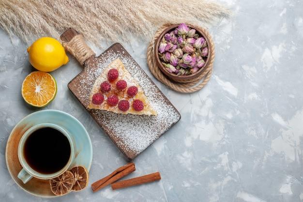 Draufsicht köstliches kuchenstück mit tasse tee und zitronen auf dem leichten schreibtischkuchenkeks süßer zuckerauflauf