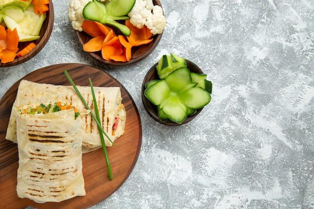 Draufsicht köstliches mahlzeit-sandwich mit gegrilltem fleisch, das mit salat auf weißraum geschnitten wird
