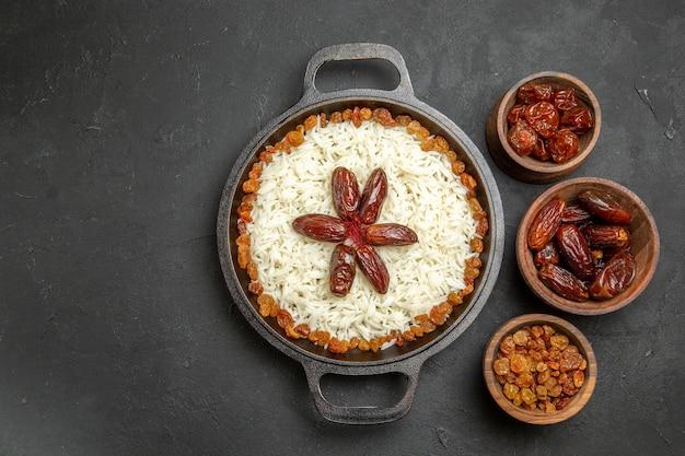 Draufsicht köstliches plov gekochtes reismahl mit rosinen in der pfanne auf der dunklen oberfläche des essensreises östliches abendessenmahlzeit