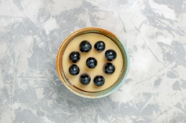 Draufsicht köstliches sahne-dessert mit trauben oben in kleinem topf auf weißer oberfläche eiscreme-dessertcreme süß