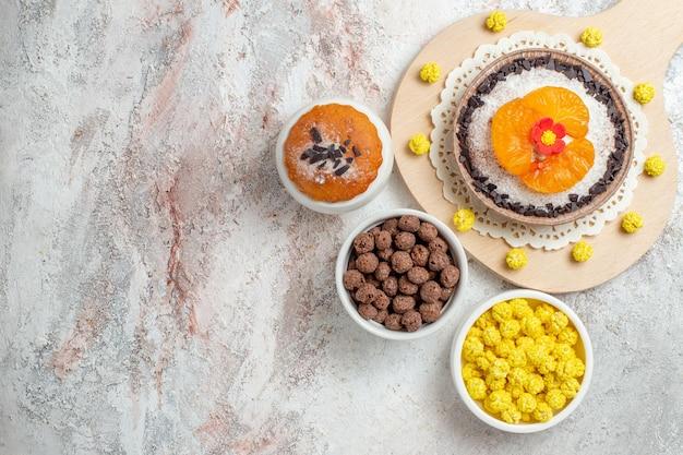 Draufsicht köstliches schokoladendessert mit mandarinen und bonbons auf weißem hintergrund creme dessert keks kuchen obst cake