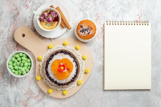 Draufsicht köstliches schokoladendessert mit tasse tee auf dem weißen hintergrund sahnekekskuchen-fruchtdessert