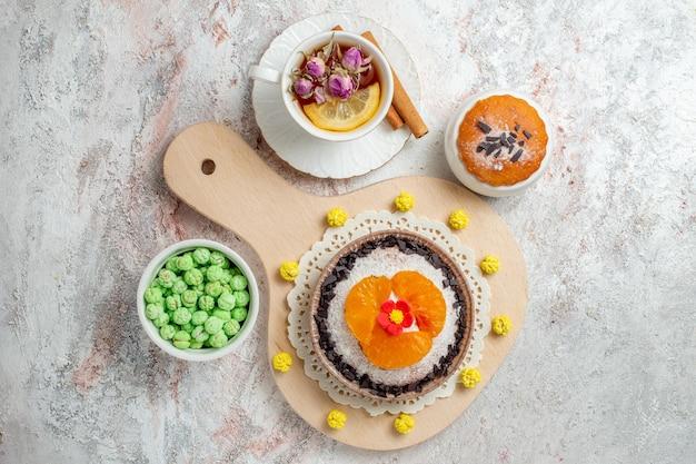 Draufsicht köstliches schokoladendessert mit tasse tee auf weißem hintergrund sahnekekskuchen-fruchtdessert