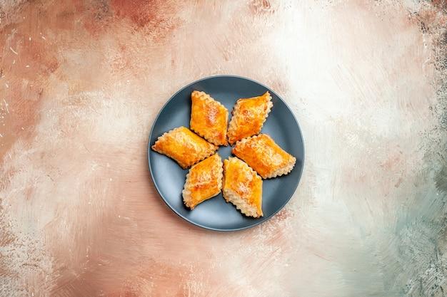 Draufsicht köstliches süßes gebäck im teller auf dem weißen tischgebäck süße kuchentorte