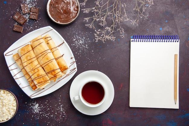 Draufsicht köstliches süßes gebäck mit schokolade und tasse tee auf dem dunklen raum