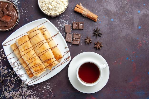 Draufsicht köstliches süßes gebäck mit schokolade und tasse tee auf dem dunklen raum Kostenlose Fotos