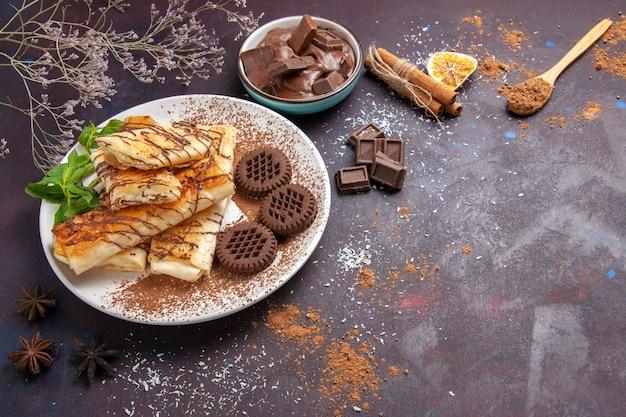 Draufsicht köstliches süßes gebäck mit schokoladenplätzchen auf dem dunklen raum