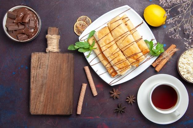 Draufsicht köstliches süßes gebäck mit tasse tee auf dem dunklen raum