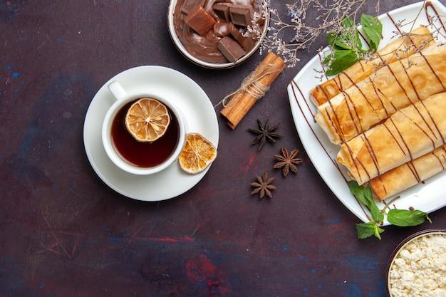 Draufsicht köstliches süßes gebäck mit tasse tee und schokolade auf dem dunklen raum