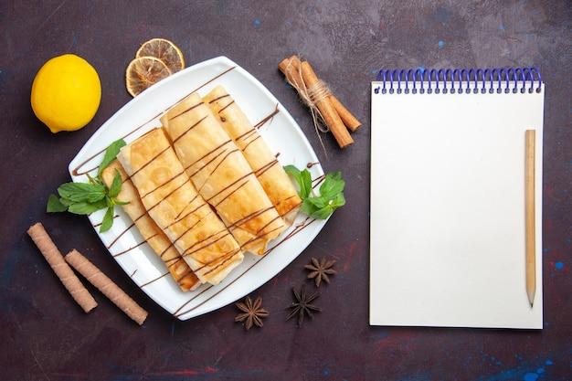 Draufsicht köstliches süßes gebäck mit zitrone auf dunklem schreibtisch