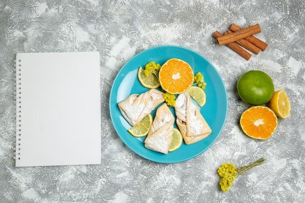 Draufsicht köstliches teiggebäck mit zitronenscheiben auf dem weißen hintergrundgebäckzucker backen kuchenteig süßes plätzchen