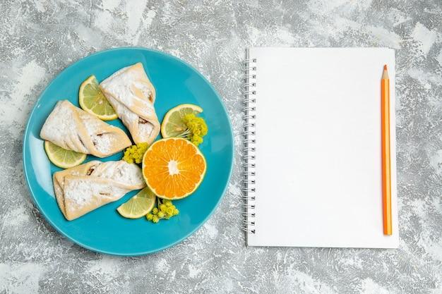 Draufsicht köstliches teiggebäck mit zitronenscheiben auf weißem hintergrundgebäckzucker backen kuchenteig süßer kuchen