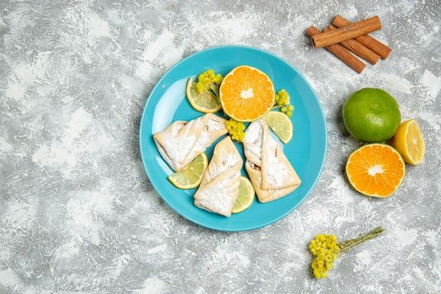 Draufsicht köstliches teiggebäck mit zitronenscheiben auf weißem hintergrundgebäckzuckerbackkuchen süßer kuchenplätzchen