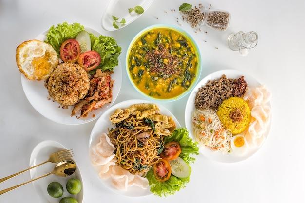 Draufsicht köstliches und gesundes indonesisches essen in weißen tellern auf weißem hintergrund
