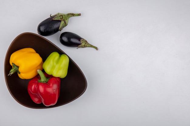 Draufsicht kopieren raum-aubergine mit farbigen paprika in der schüssel auf weißem hintergrund