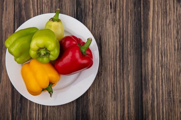 Draufsicht kopieren raum farbige paprika auf einem teller auf einem hölzernen hintergrund