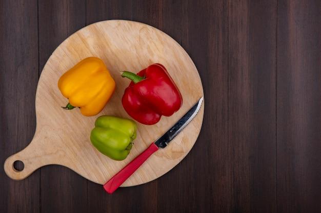 Draufsicht kopieren raum farbige paprika auf schneidebrett mit messer auf holzhintergrund