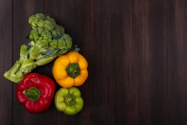 Draufsicht kopieren raum farbige paprika mit brokkoli auf hölzernem hintergrund