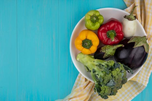 Draufsicht kopieren raum farbige paprika mit brokkoli und auberginen auf einem teller mit einem gelben karierten handtuch auf einem türkisfarbenen hintergrund