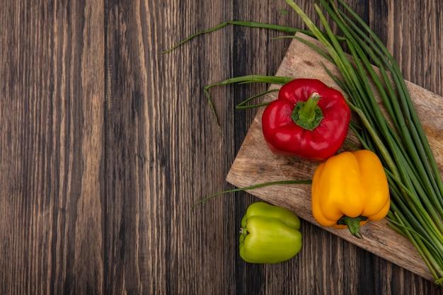 Draufsicht kopieren raum farbige paprika mit frühlingszwiebeln auf einem schneidebrett auf hölzernem hintergrund
