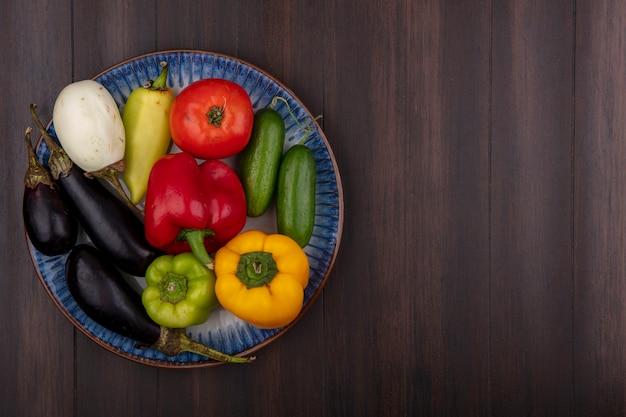 Draufsicht kopieren raum farbige paprika mit gurken und tomaten auberginen auf einem teller auf holzhintergrund