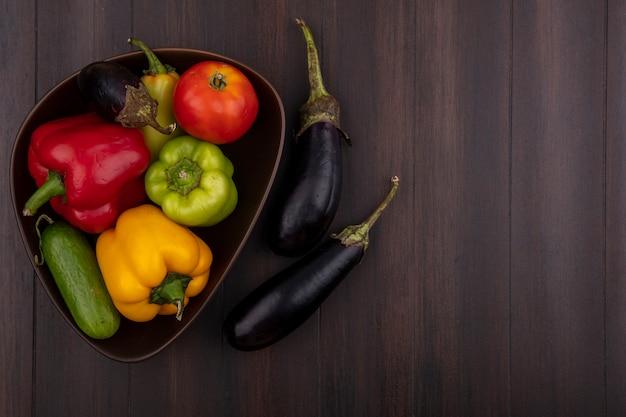 Draufsicht kopieren raum farbige paprika mit gurken und tomaten in schüssel mit auberginen auf hölzernem hintergrund