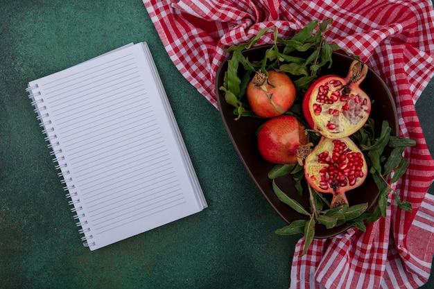 Draufsicht kopieren raum granatapfel mit zweigen in einer schüssel mit einem karierten roten handtuch und notizblock auf einem grünen hintergrund