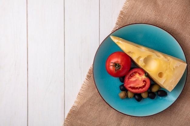 Draufsicht kopieren raum maasdam käse mit tomaten und oliven auf einem blauen teller auf einer beigen serviette auf einem weißen hintergrund
