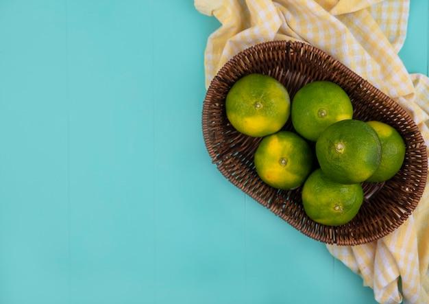 Draufsicht kopieren raum-mandarinen in einem korb auf einem gelben karierten handtuch auf einer blauen wand