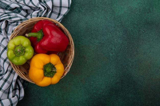 Draufsicht kopieren raum-paprika in einem korb auf einem grünen hintergrund