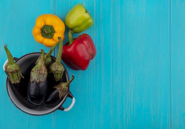Draufsicht kopieren raum schwarze auberginen in einem topf mit farbigem paprika auf einem türkisfarbenen hintergrund