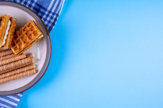 Draufsicht kopieren raum süße brötchen mit waffeln auf teller auf küchentuch auf blau