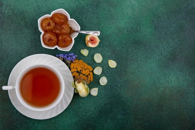 Draufsicht kopieren raum tasse tee mit feigenmarmelade und blumen auf grünem hintergrund