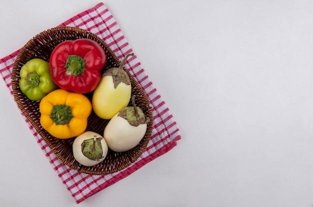 Draufsicht kopieren raum weiße aubergine mit farbigen paprika in einem korb auf einem roten karierten handtuch auf einem weißen hintergrund