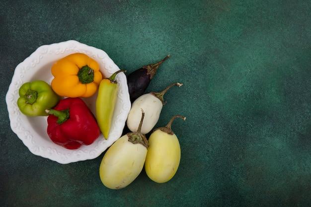Draufsicht kopieren raum weiße und schwarze aubergine mit paprika auf einem teller auf grünem hintergrund