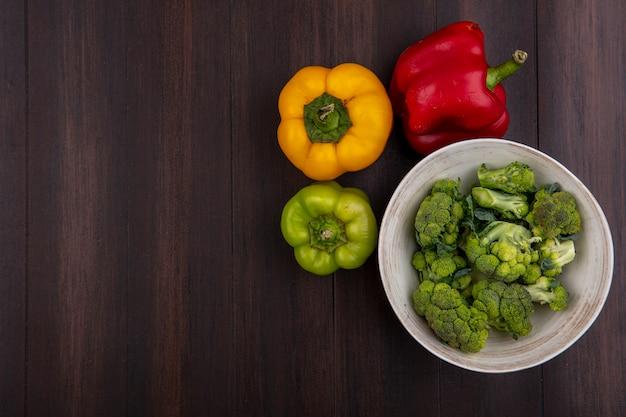 Draufsicht kopieren raumbrokkoli in der schüssel mit paprika auf hölzernem hintergrund