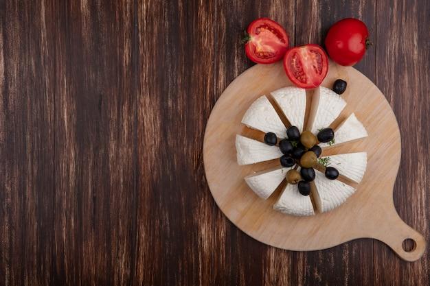 Draufsicht kopieren raumfeta-käsescheiben mit oliven auf einem ständer und tomaten auf hölzernem hintergrund