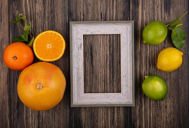 Draufsicht kopieren raumgrapefruit mit orangen-zitronen-limetten und grauem rahmen auf hölzernem hintergrund
