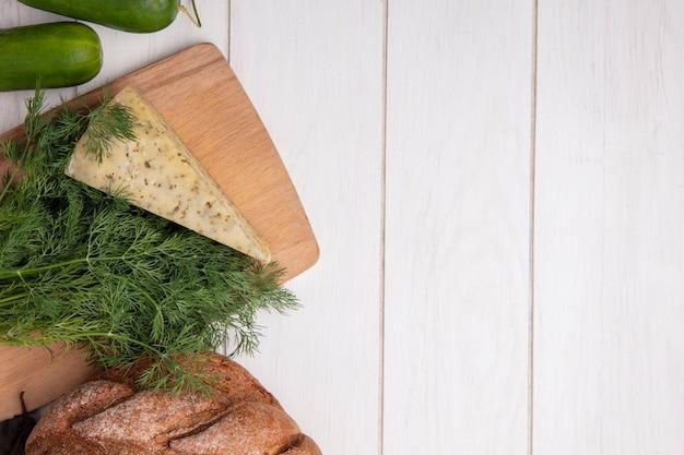 Draufsicht kopieren raumgurken mit einem laib schwarzbrot mit käse und dill auf weißem hintergrund
