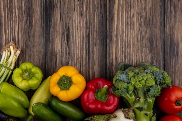 Draufsicht kopieren raumgurken mit farbigem paprikabrokkoli und tomaten auf hölzernem hintergrund