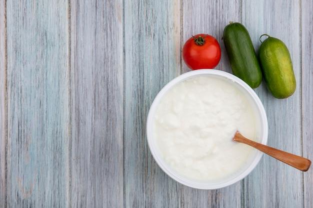 Draufsicht kopieren raumjoghurt in schüssel mit holzlöffel tomate und gurke auf grauem hintergrund