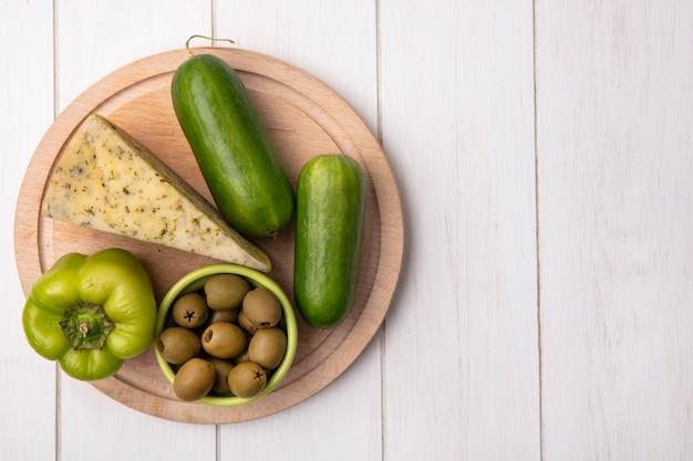 Draufsicht kopieren raumkäse mit gurken und paprika auf einem ständer mit oliven auf einem weißen hintergrund