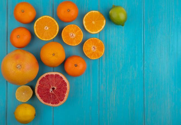 Draufsicht kopieren raumkalk mit keilen und ganzer orange und grapefruit auf türkisfarbenem hintergrund