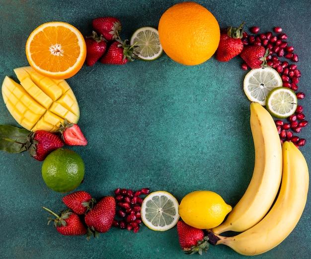 Draufsicht kopieren raummischung der früchte mango banane erdbeeren zitronenorange auf einem grünen hintergrund