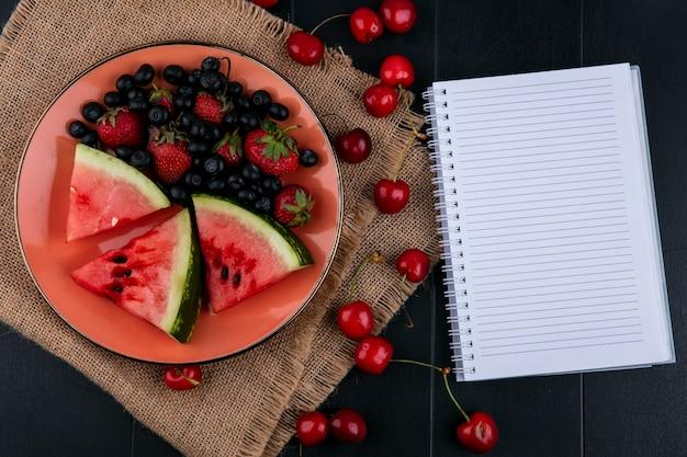 Draufsicht kopieren raumnotizbuch mit scheiben von wassermelonenerdbeeren und -blaubeeren auf einem teller mit kirschen auf einem schwarzen hintergrund