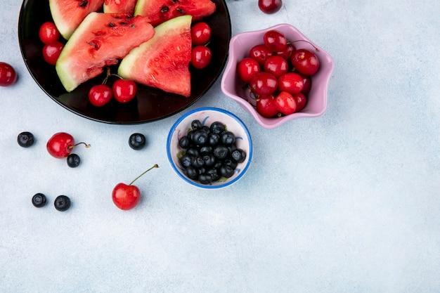 Draufsicht kopieren raumscheiben der wassermelone auf einem teller mit blaubeeren und kirschen