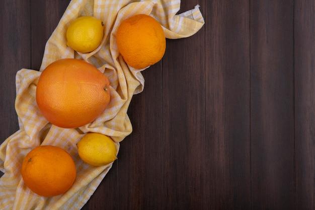Draufsicht kopieren raumzitronen mit orange und grapefruit auf gelbem kariertem handtuch auf hölzernem hintergrund