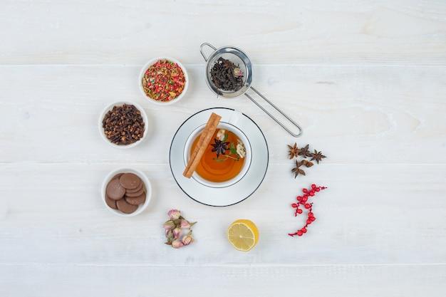 Draufsicht kräutertee und kekse mit teesieb, kräutern und gewürzen auf weißer oberfläche