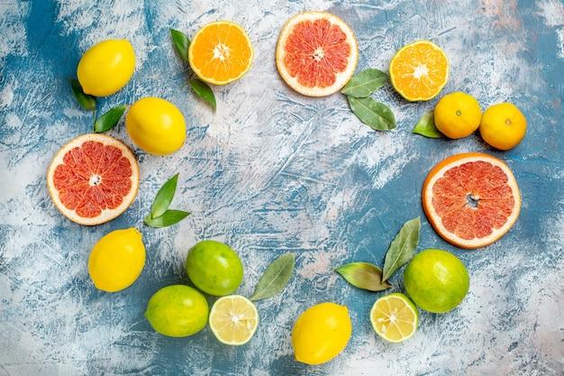 Draufsicht kreisreihe zitrusfrüchte zitronen grapefruits mandarinen auf blau weißem tisch